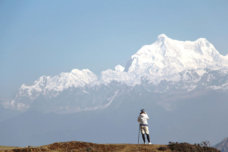 Full length of man walking on mountain against clear sky