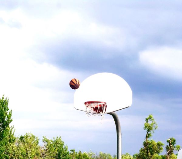 Low angle view of basketball and hoop against cloudy sky