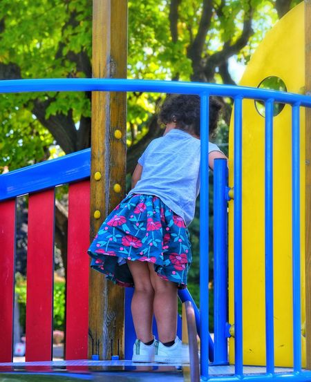 Rear view of girl playing on playground