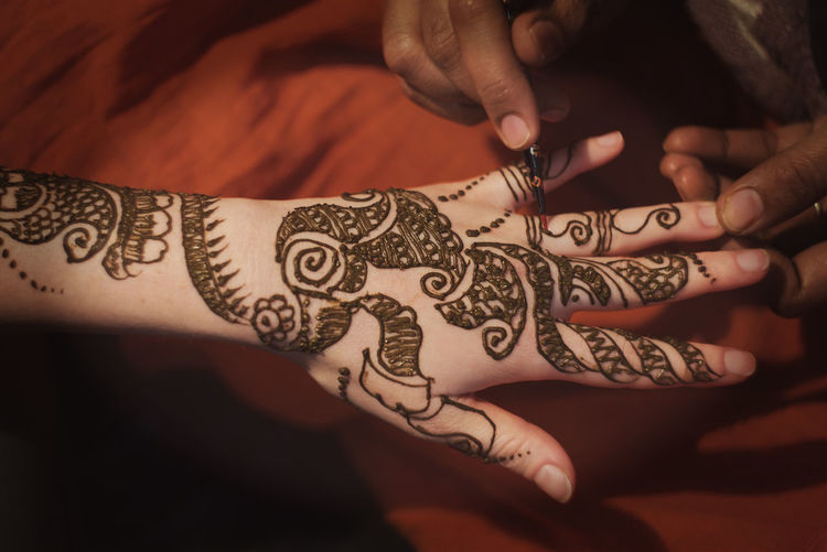 Midsection of woman applying henna on cropped hand