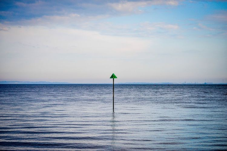 Pole in sea against sky