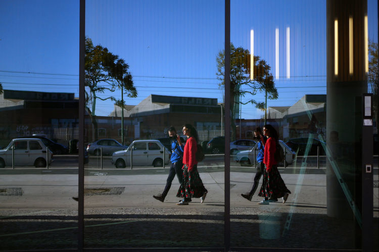 Reflection Of Couple Walking On Footpath