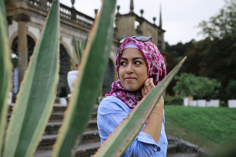 // beauty in Nature // Happy Portrait Of A Woman Profile Adult Casual Clothing Day Focus On Foreground Front View Headscarf Hijab Leisure Activity Lifestyles Looking At Camera Muslim One Person Outdoors Plant Portrait Real People Standing Style Waist Up Women Young Adult Young Women