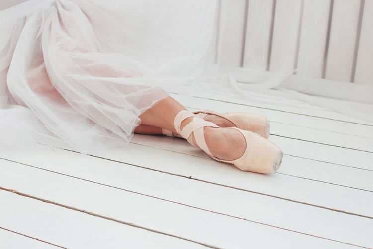 Young woman authentic ballerina ballet dancer in pointe shous sitting on white floor One Person Real People Low Section Human Body Part Human Leg Body Part Women White Color Lifestyles High Angle View Adult Indoors  Flooring Human Foot Shoe barefoot Sitting Day Wood Tiled Floor Ballet Dancer