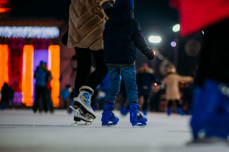 Low section of person with child ice skating on rink at night