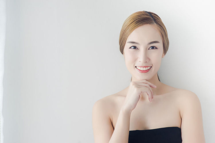 Close-Up Portrait Of Young Woman Smiling Against White Background