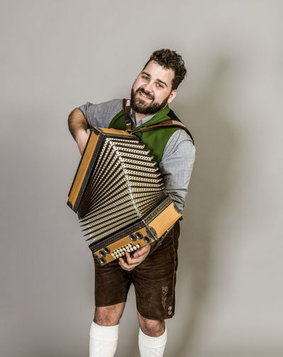 Musician Costume Leather Trousers Tradition Traditional Austria Green Pose Accordion Man Young Shorts Friendly Proud Happy Play Music Fun Joy Single One Background Copy Space Studio Entertainment Mountains Shirt STAND Hobby Leisure Cool Three Quarter Length Studio Shot Standing Indoors  One Person Casual Clothing Looking At Camera Portrait Gray Background Front View Gray Young Adult Holding Emotion Arts Culture And Entertainment Smiling White Background Hairstyle
