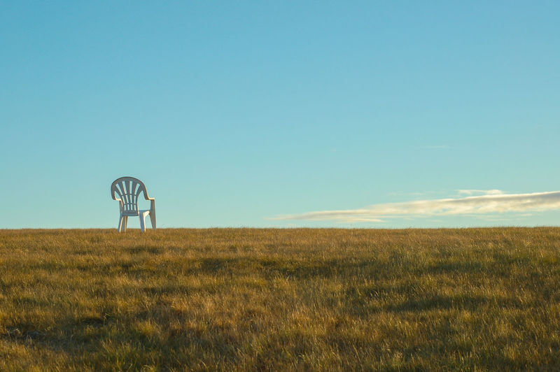 Scenic View Of Chair On A Grassy Field