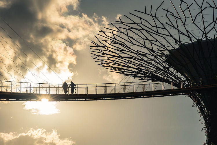 Low angle view of silhouette people on footbridge against sky