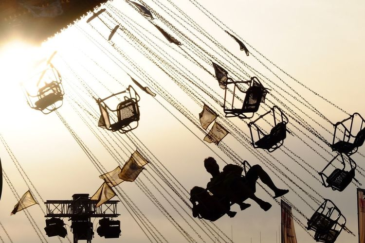 Low angle view of people sitting on chain swing ride against sky during sunset