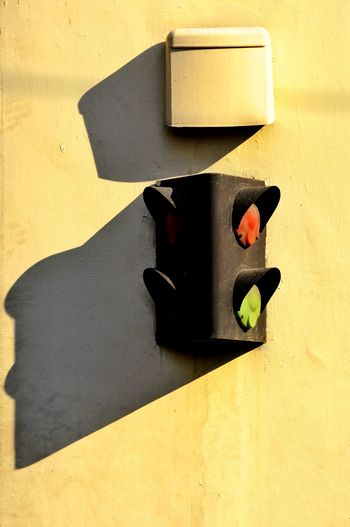 Low angle view of road signal mounted on wall