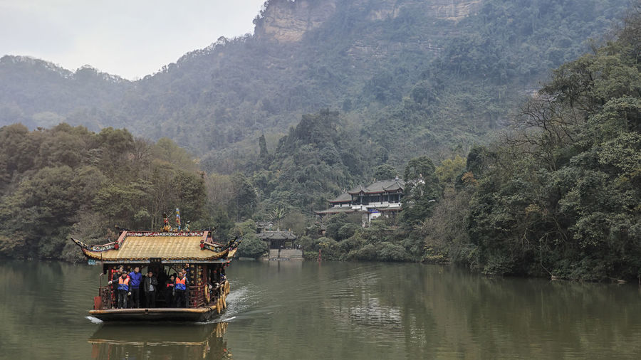Dujiangyan, China - December 12, 2018: Tourists on a boat and Buddhist temple in the Qingcheng mountain area close to Chengdu Chengdu China ASIA Dujiangyan Buddhist Temple Qingcheng Park Water Mountain Tree Group Of People Plant Nature