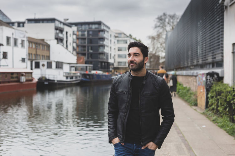 Man looking away while standing by canal in city