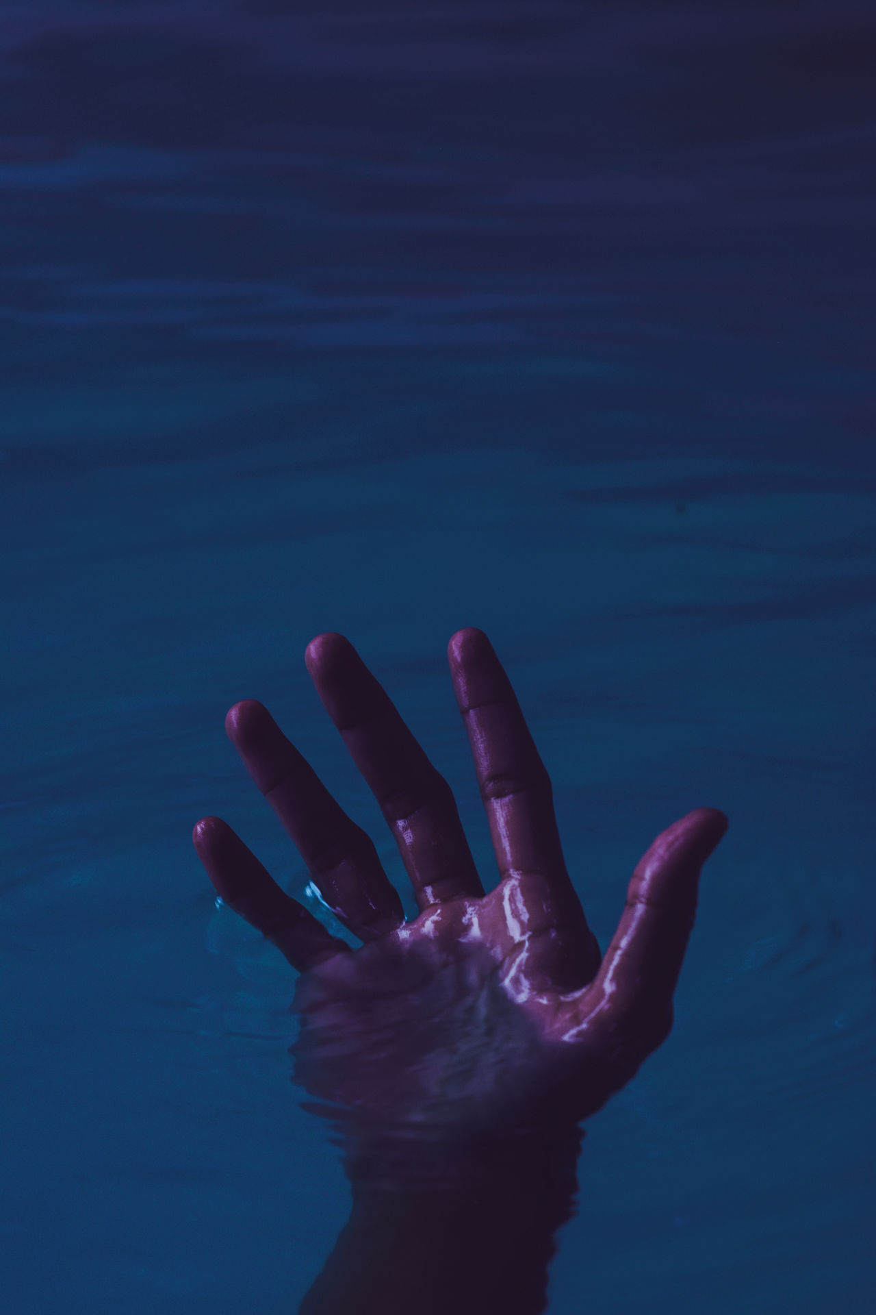 Cropped hand drowning in lake at night