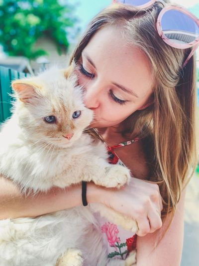 Close-up of young woman kissing cat