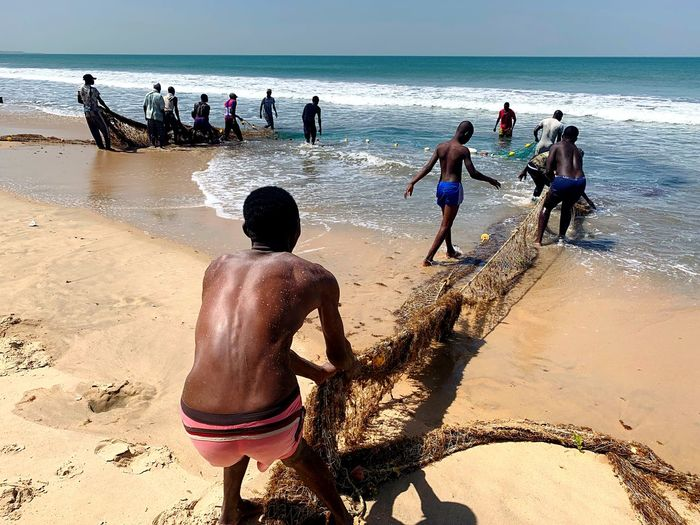 Fishermen on the beach in The Gambia Hard Work Pulling Fishing Net Fishermen Water Sea Beach Land Group Of People Real People Men Sand Lifestyles Shirtless Nature Horizon Over Water