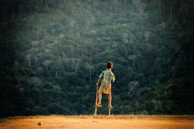 Rear View Of Boy Standing On Stilts In Field