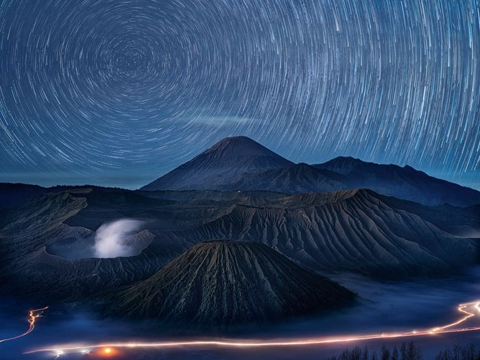 Scenic view of volcanic crater against star trail at night