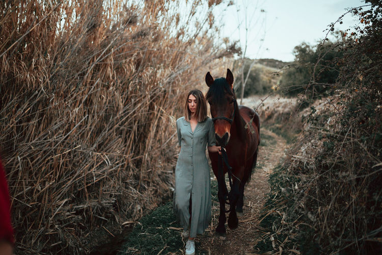 Full length of women walking with horse