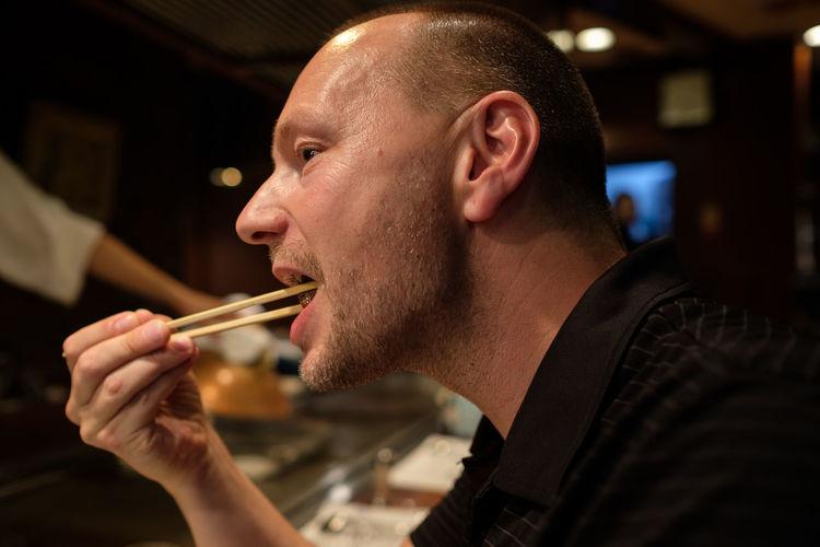 Close-up of man eating with chopsticks