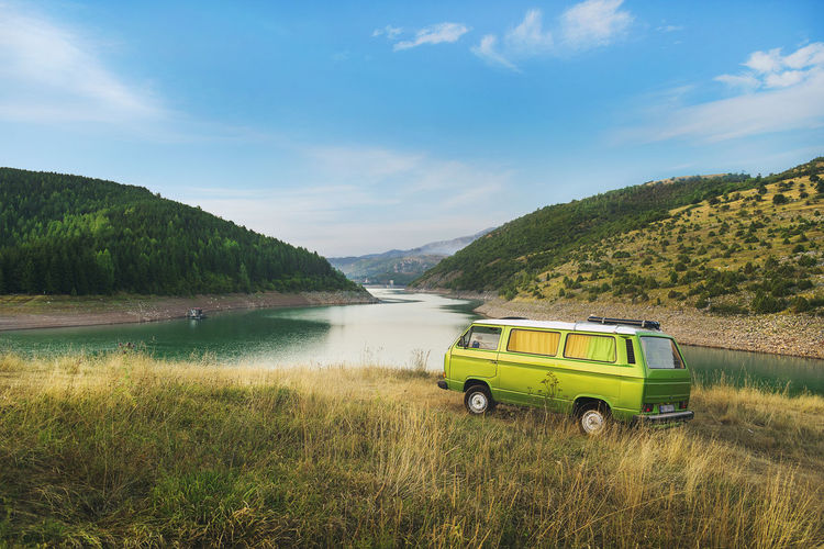 Travel Trailer Parked On Grassy Riverbank Against Blue Sky