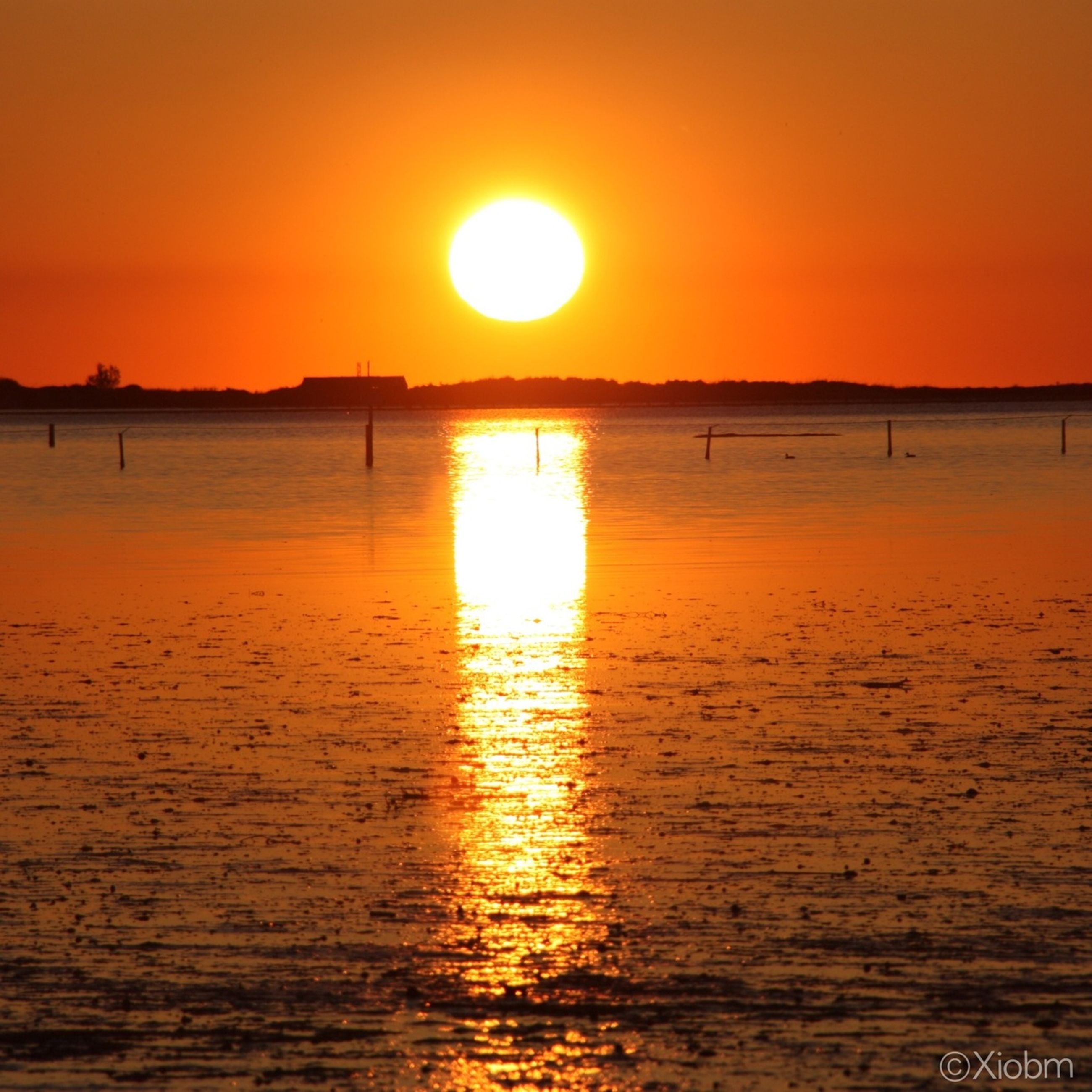 sunset, sun, orange color, water, scenics, tranquil scene, tranquility, beauty in nature, sea, idyllic, reflection, silhouette, nature, waterfront, clear sky, sunlight, sky, rippled, horizon over water, romantic sky