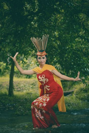 Young Woman Wearing Traditional Clothing Dancing In Forest