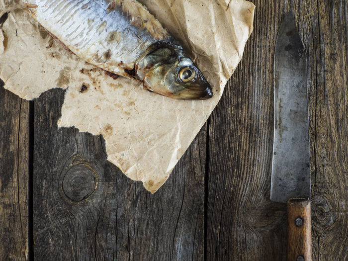 Directly above shot of herring on paper at table