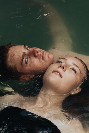High angle view of couple floating on lake