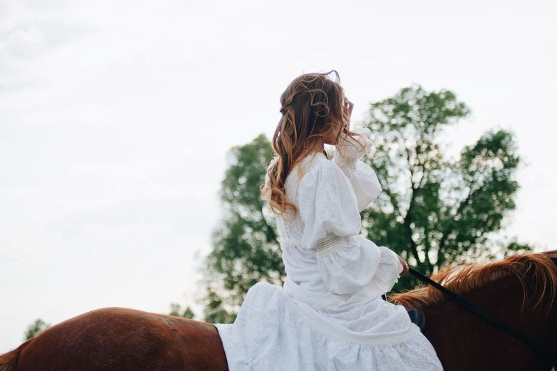 Young woman riding horse against sky