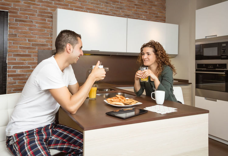 Happy young love couple speaking and having a good breakfast in the home kitchen Family Fruit Girlfriend Thirties Relaxing Husband Boyfriend 30s Wife Relationship Adult Lifestyle Interior Love Cup Caucasian Healthy Two Coffee Glass Orange Girl Juice Meal Drink Together Young Woman Kitchen Man Indoors  Food Morning Technology Newspaper Digital Tablet News Smiling Cheerful Happiness Smile Happy Male Home People Female Couple Breakfast