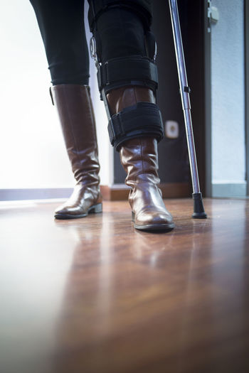 Low section of handicapped man with walking cane standing on parquet floor