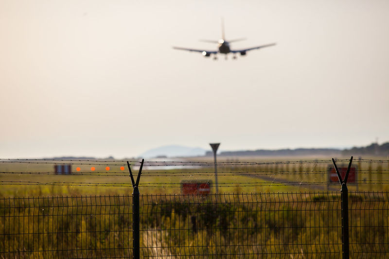 Airplane landing on sunset. Budapest, Hungary Air Airplane Airport Airport Fence Airport Runway Day Fence Fences Flying Helicopter Horizon Over Land Journey Landscape Mid-air Mode Of Transport Nature No People Outdoors Runway Rural Scene Sky