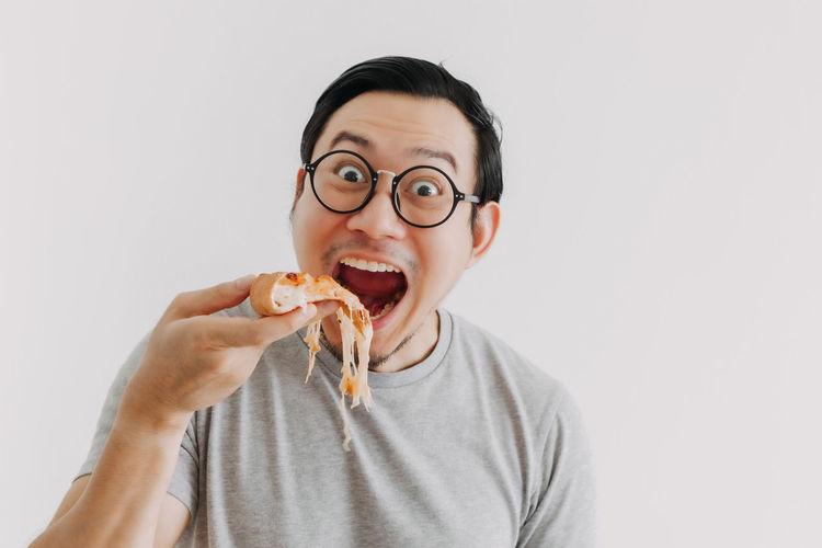 Portrait of smiling man holding ice cream against white background