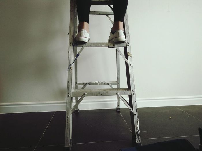 Low section of woman standing on step ladder against wall