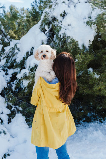 Woman with dog standing in snow