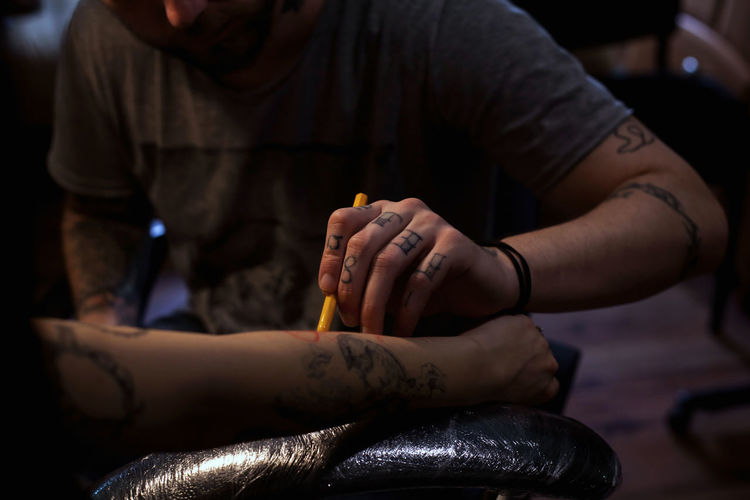 Midsection of artist drawing tattoo on mid adult woman hand in studio