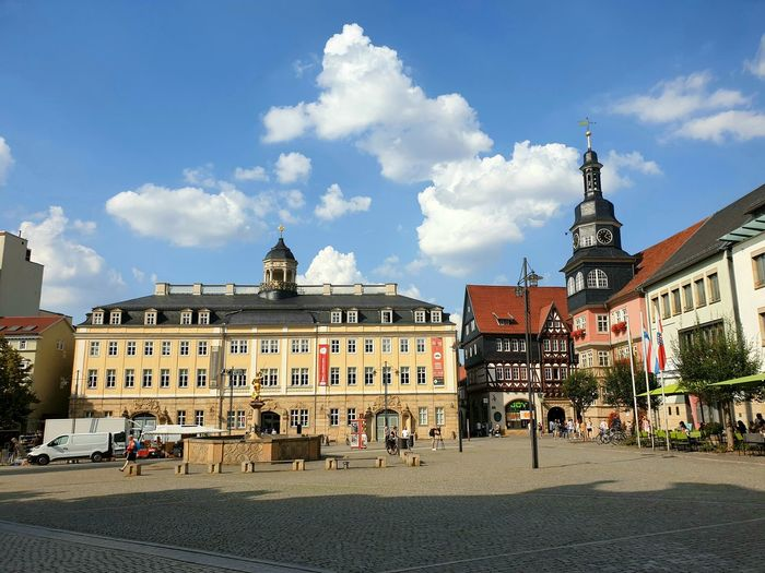 Eisenach city center town square with fountain under blue sky white clouds...