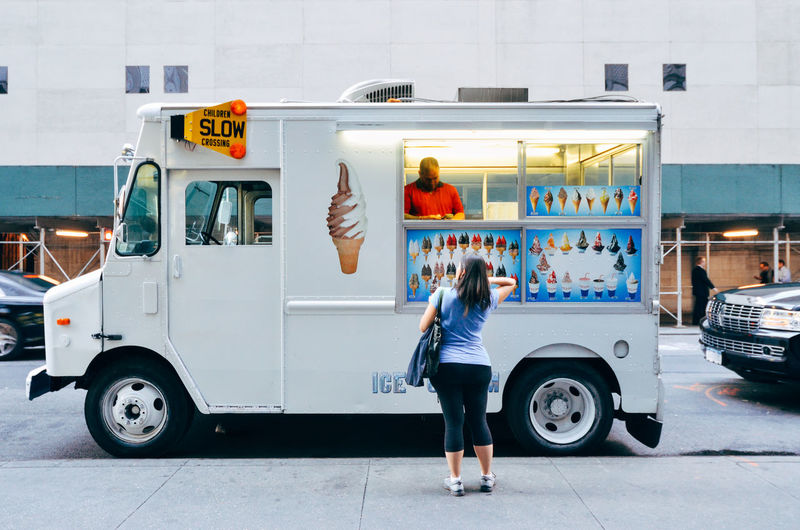 Rear View Of Woman Buying From Food Truck Salesman