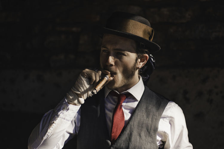 a mid level shot of a man smoking a cigar. Business Clothing Formalwear Front View Hat Headshot Holding Indoors  Males  Men Menswear Necktie One Person Portrait Real People Suit Well-dressed Young Adult Young Men