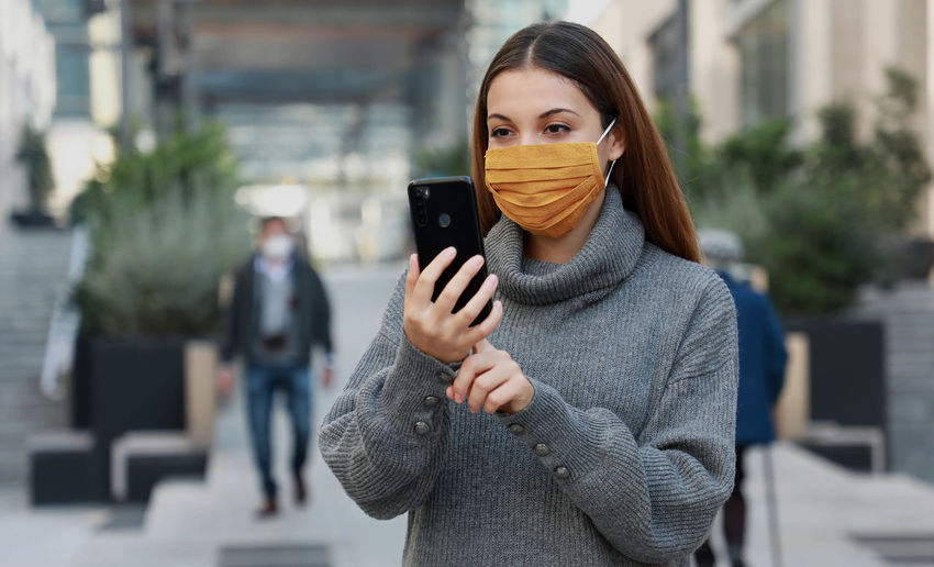 Young woman wearing mask using phone while standing outdoors