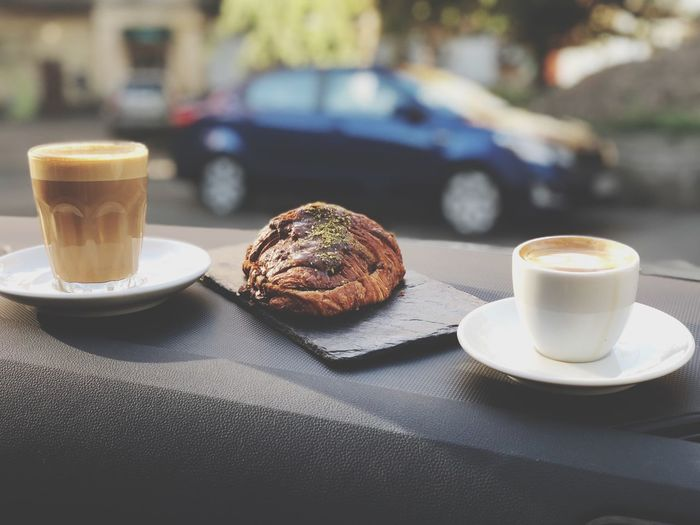 Croissant amid coffees served on table