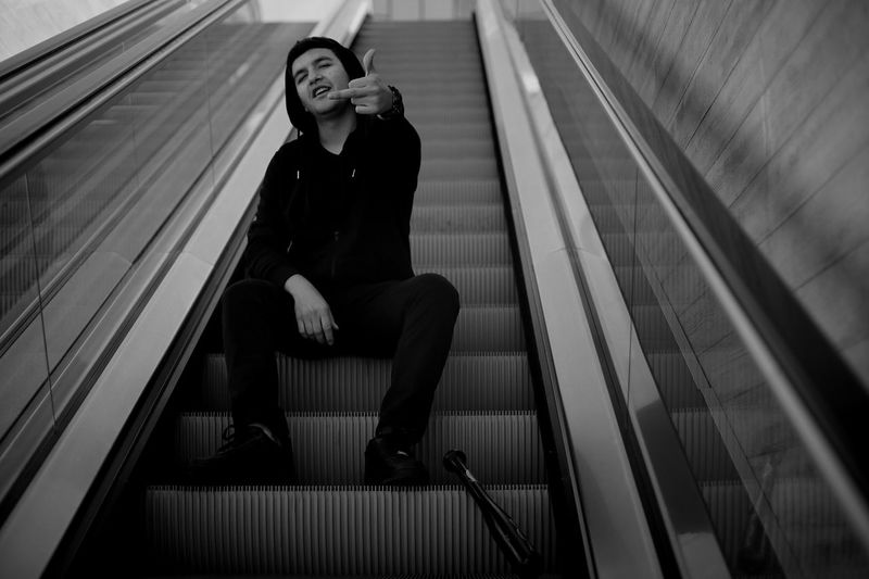 Portrait of man sitting on escalator while showing obscene gesture at subway station