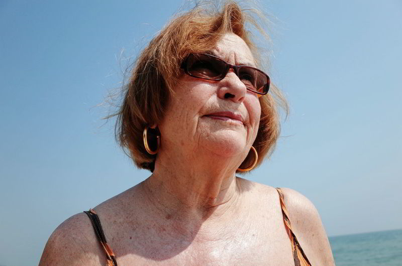 Close-up senior woman wearing sunglasses against clear sky