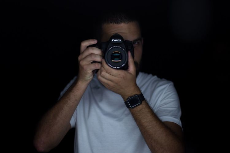 Midsection of man holding camera while standing against black background
