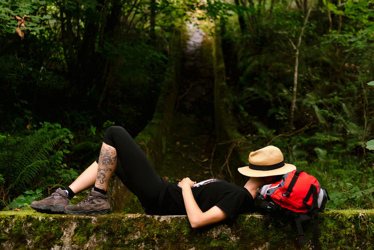Midsection of woman sitting in forest