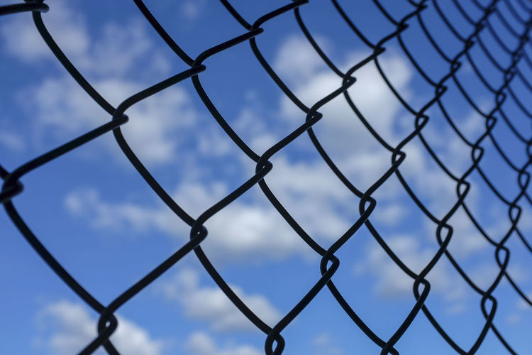 Blue sky with white clouds seen through a chainlink fence. Chainlink Fence Full Frame Backgrounds Sky Blue Pattern No People Cloud - Sky Safety Fence Security Protection Boundary Barrier Border Hope - Concept Dreams Depression Blocked View Obstacles Freedom Limits The Great Outdoors - 2019 EyeEm Awards