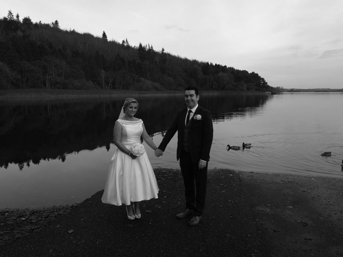 Portrait of wedding couple holding hands while standing at lakeshore against sky