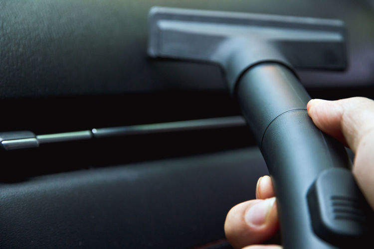 Cropped image of man hand cleaning car with vacuum cleaner