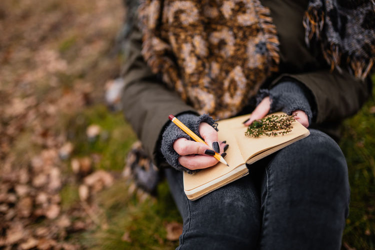 Midsection of woman writing in diary at forest